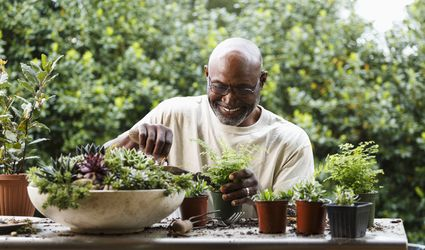 Black man gardening at table outdoors