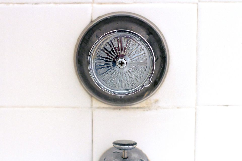 Shower knob and faucet mounted to a wall.