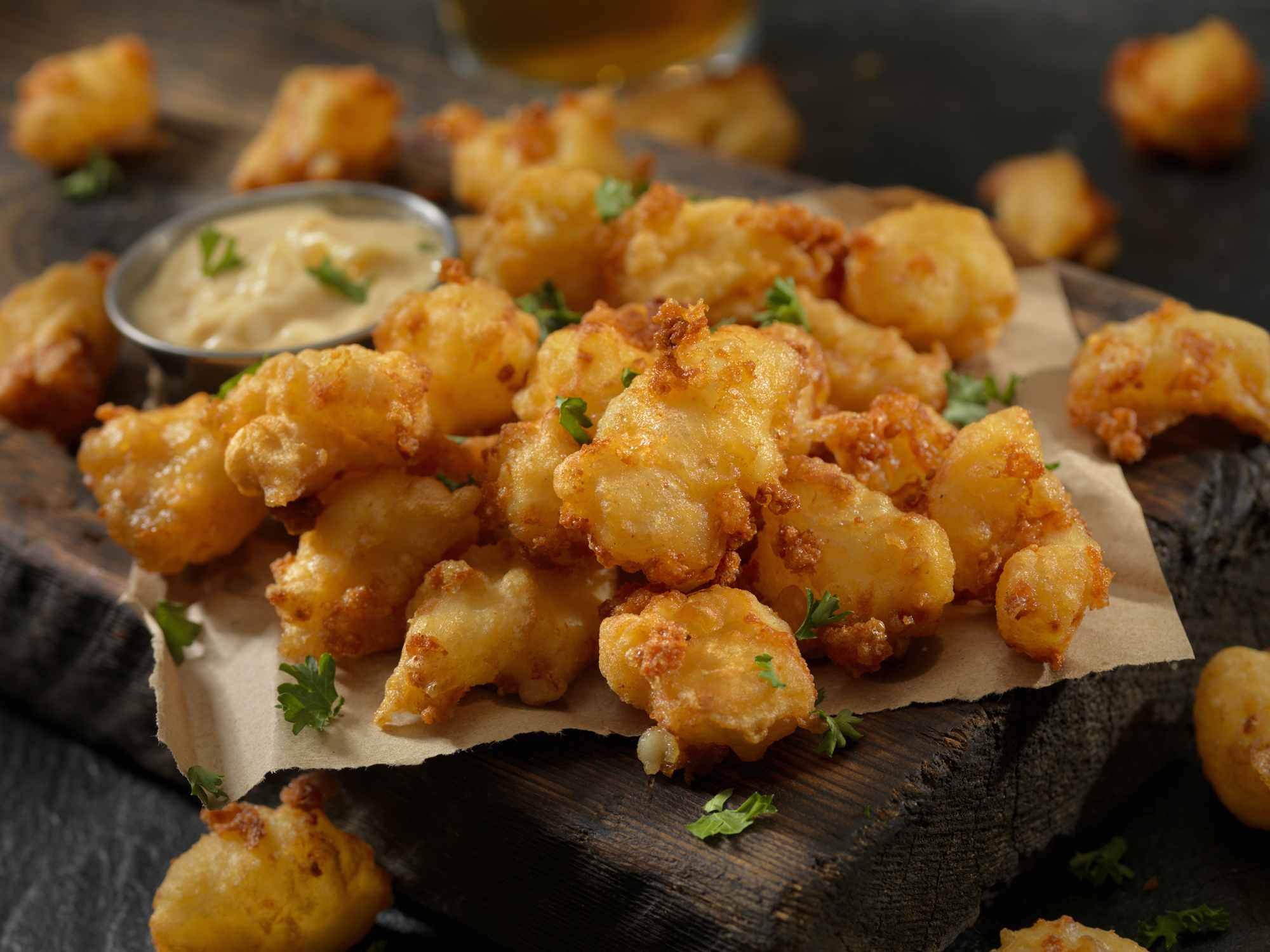A plate of cheese curds with dipping sauce.