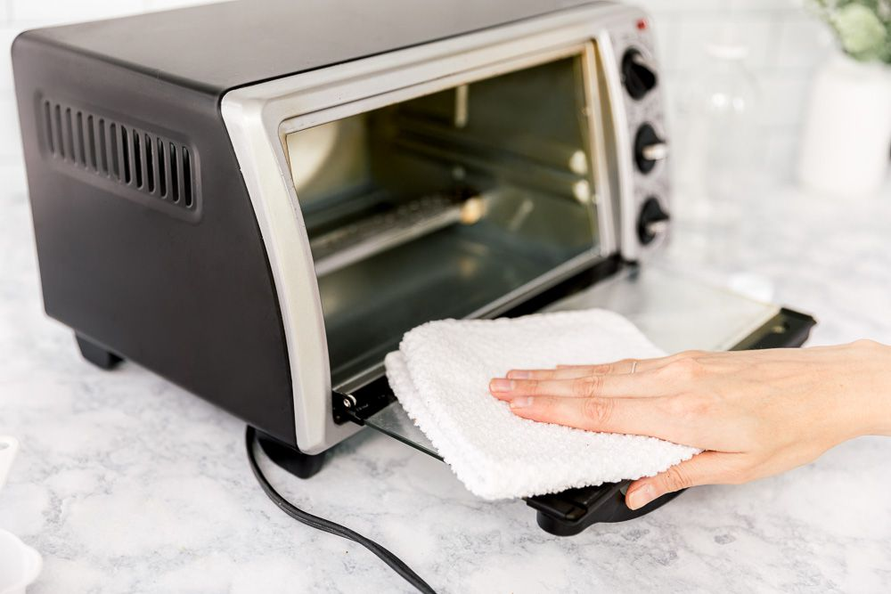 cleaning the glass door of the toaster oven
