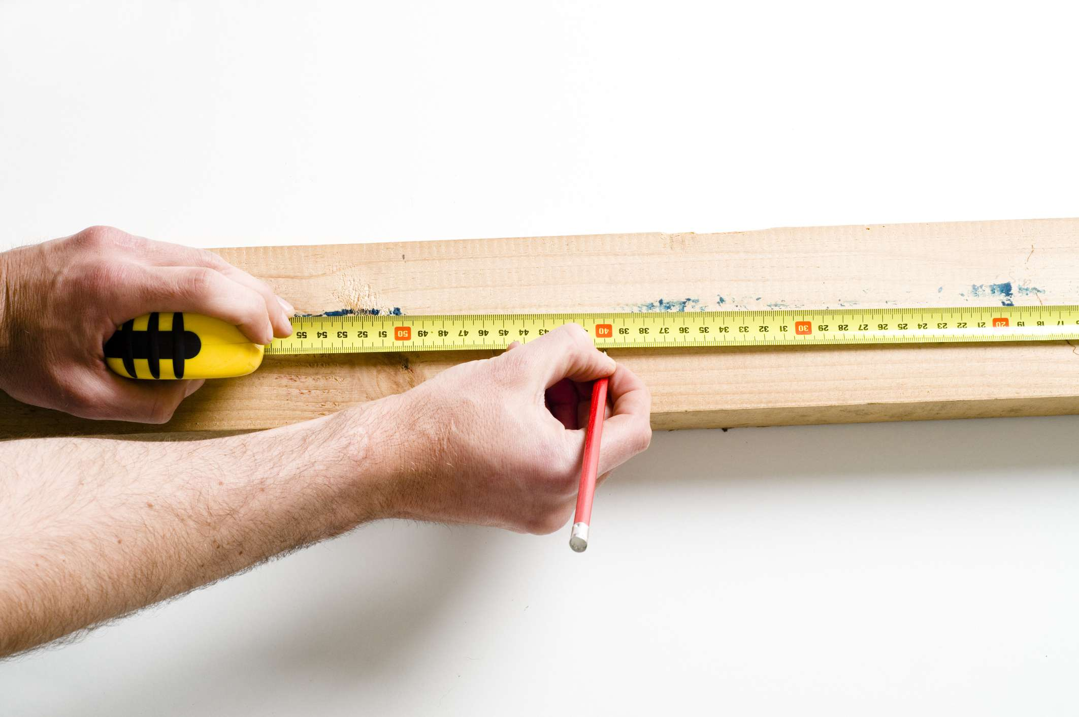 Hands measuring and marking wood