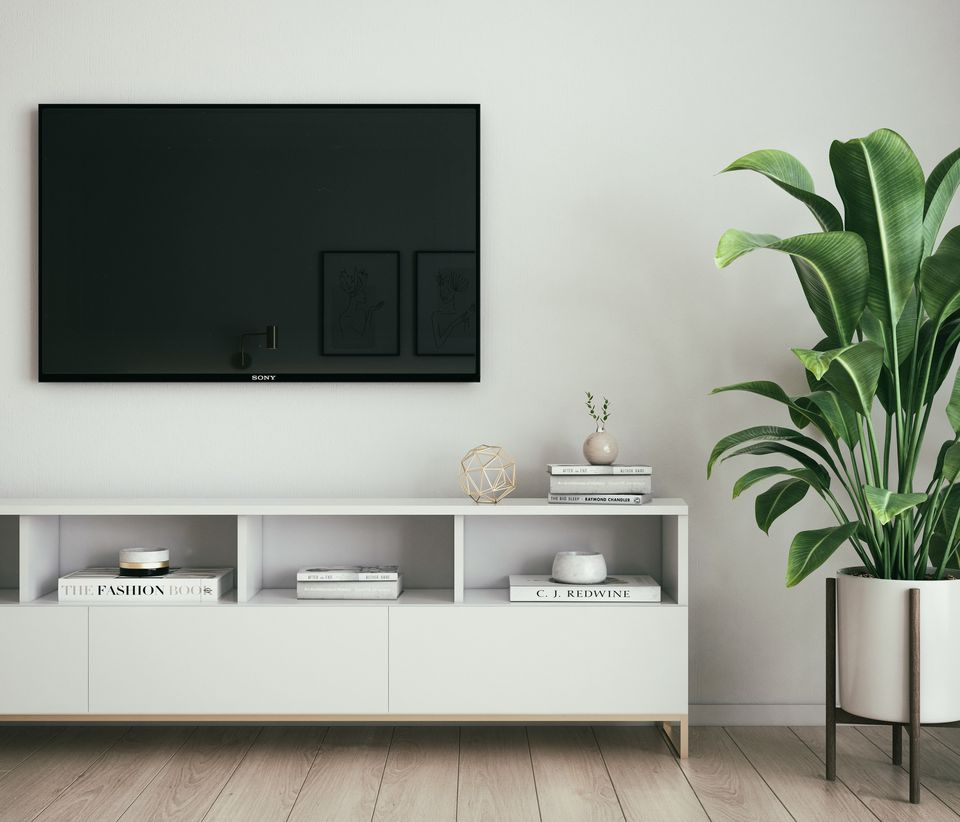 TV above a console and next to a plant