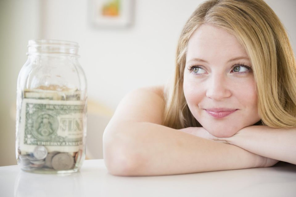 Woman with jar of money, looking away in thought
