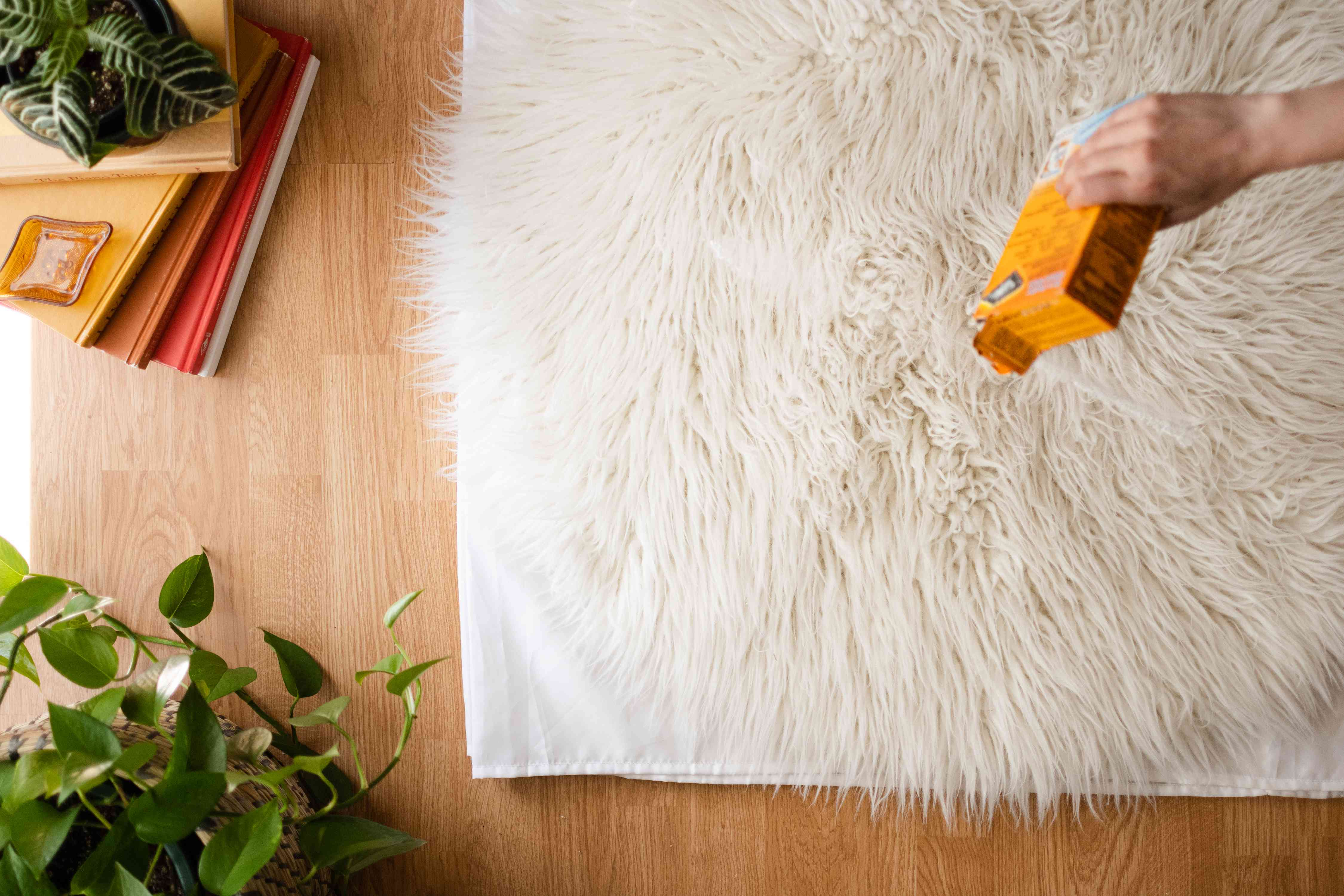 Baking soda poured on to white shag rug to brighten and deodorize