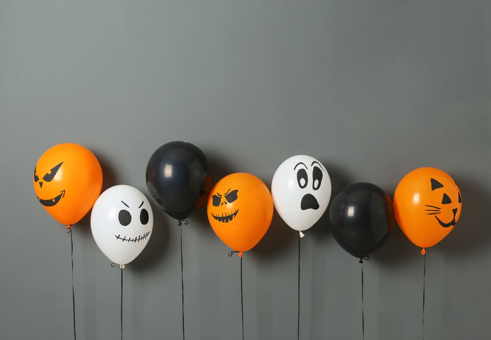 White, orange, or black balloons for Halloween party on gray background.