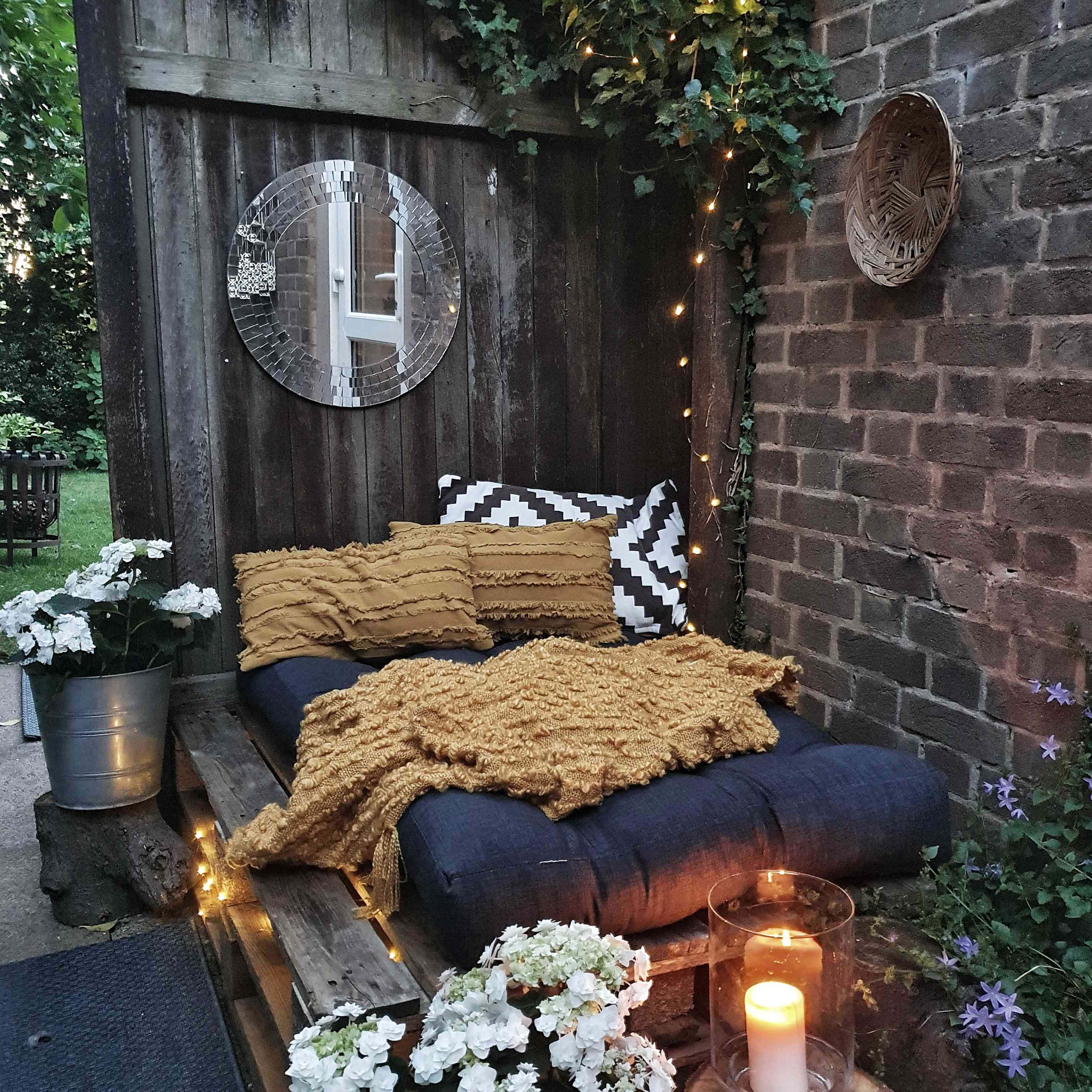 An outdoor bed features a distressed wood fence, a brick wall, textured bedding and lots of flowers