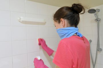 woman cleaning shower wall