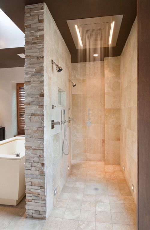 A stone bathroom with walk-in double shower