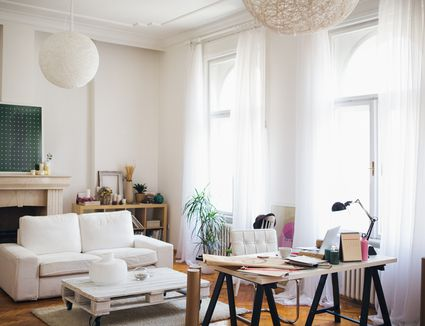 Light and bright living room with lofted ceiling and white furniture