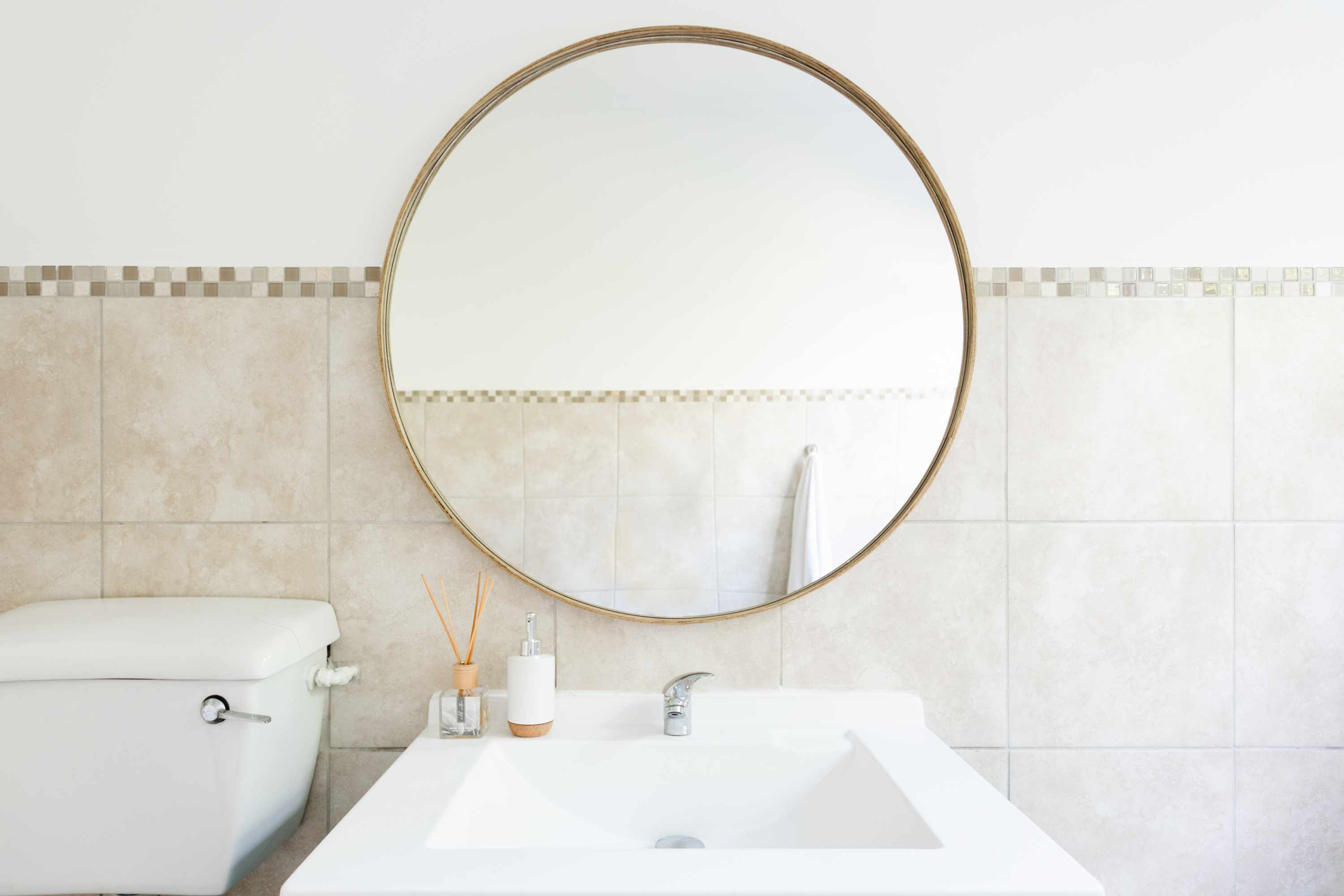 Guest bathroom with rounded mirror with cream-colored marble wall tiles and off-white walls