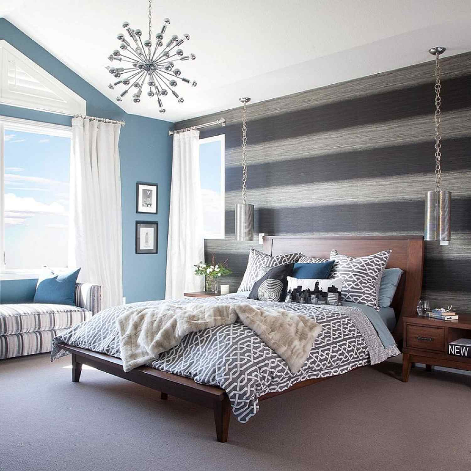 Gray striped wall in contemporary bedroom with bed and decorative ceiling light fixture..