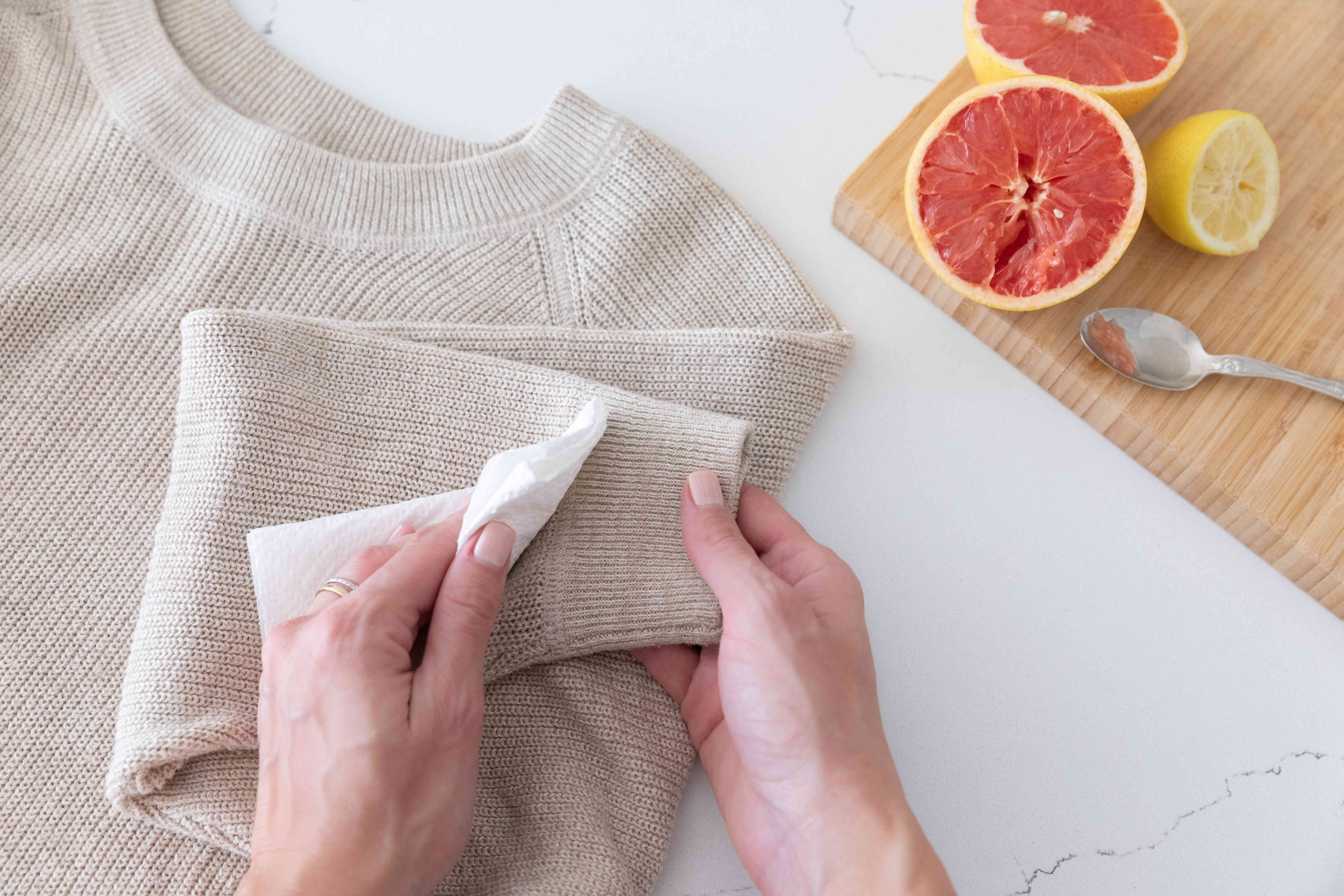 White cloth dipped in water blotting dry clean clothing sleeve to remove citrus stain