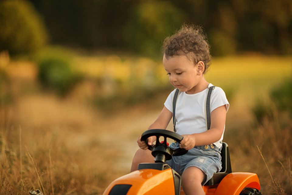 Little boy riding on toy tractor