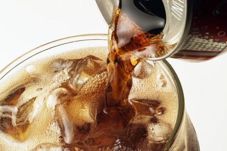 Pouring Cola Into A Gl With Ice Cubes From Can
