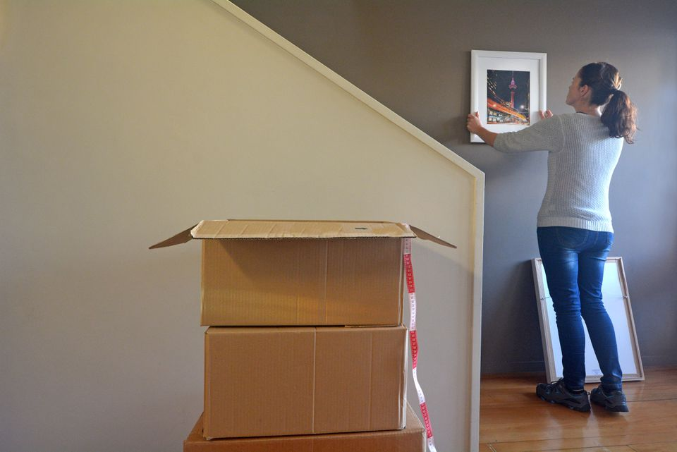 Woman Unpacking Boxes and Hanging a Picture on Her new Home Wall