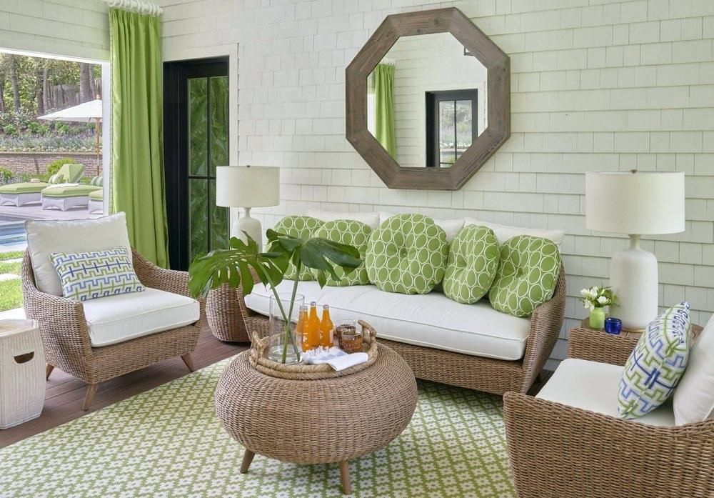 casa de la piscina con muebles de mimbre y almohadas verdes