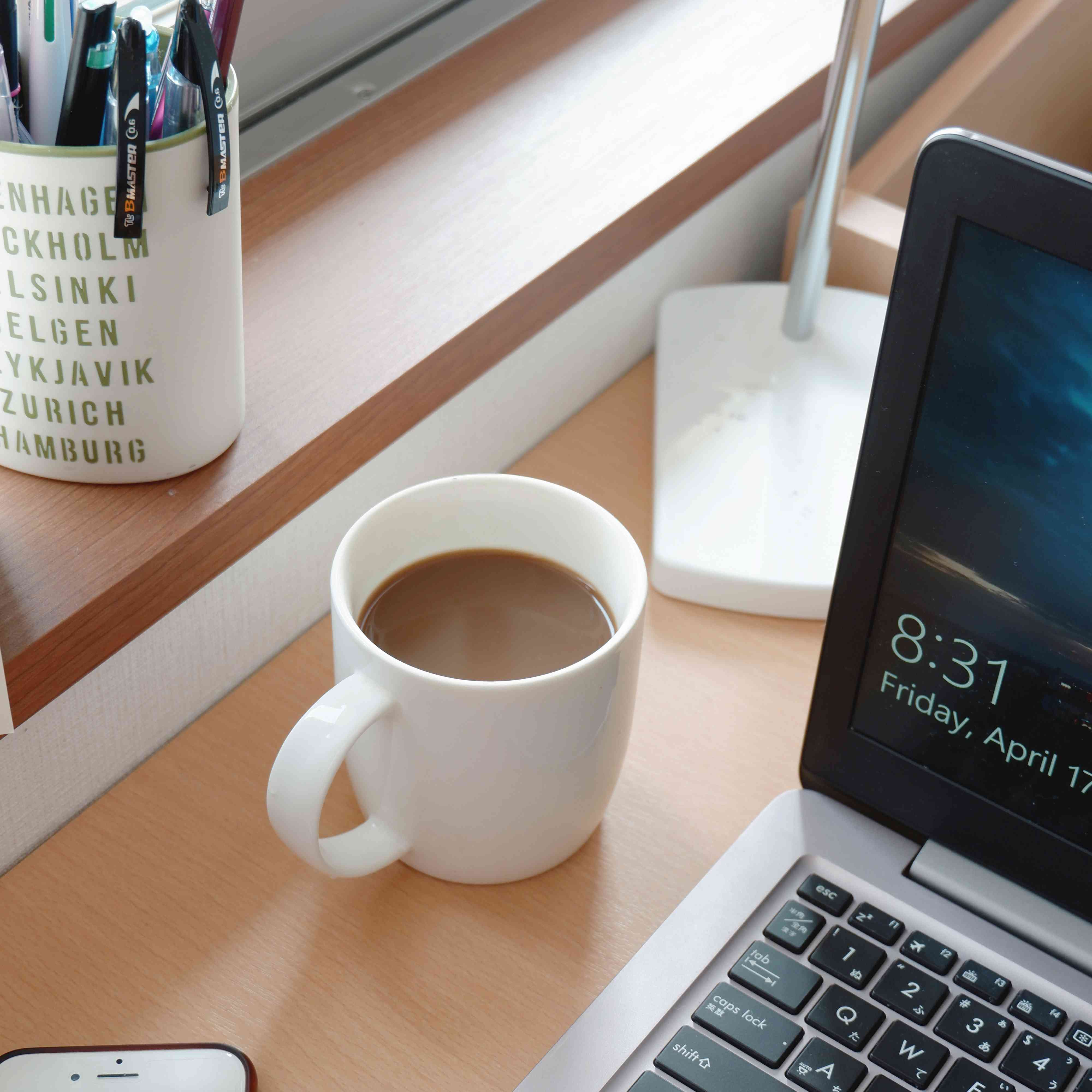 desk with laptop, pencils, cell phone, and coffee cup