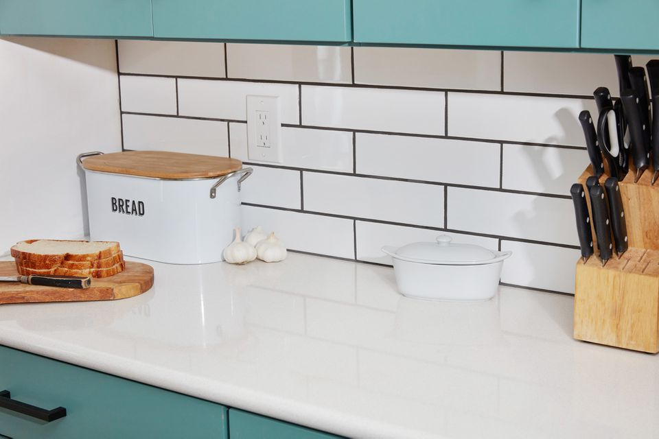 White subway tile on kitchen wall next to bread box with slices of bread in front and knives