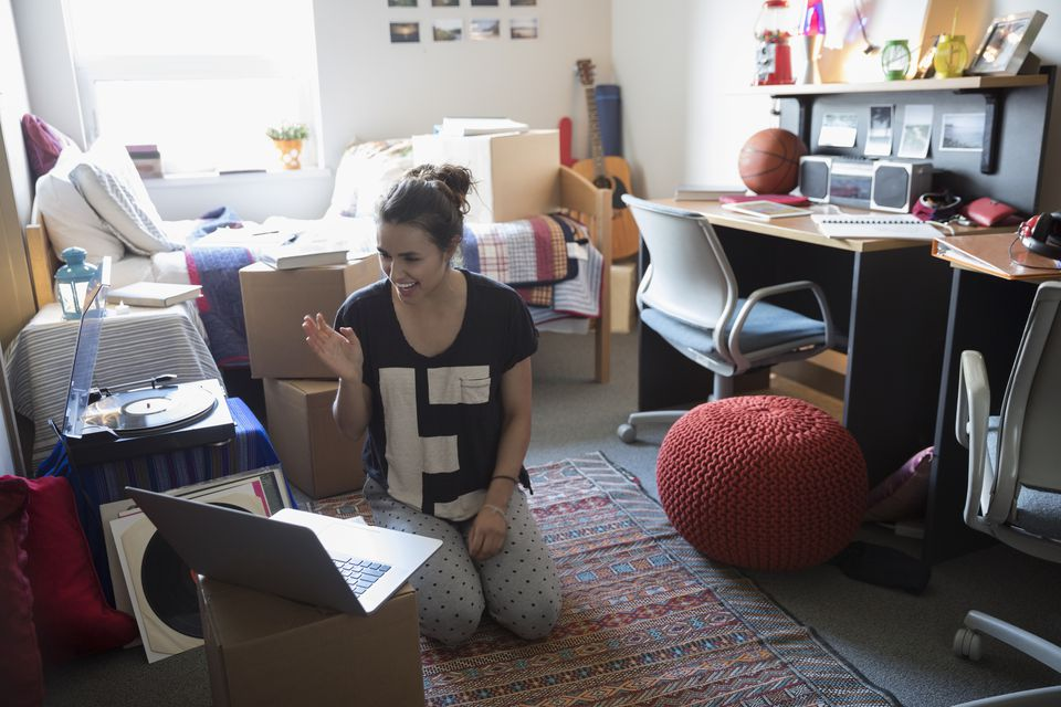 Female college student waving, video chatting with laptop in dorm room