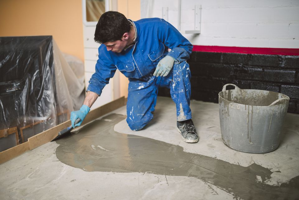 Bricklayer applying wet cement on floor