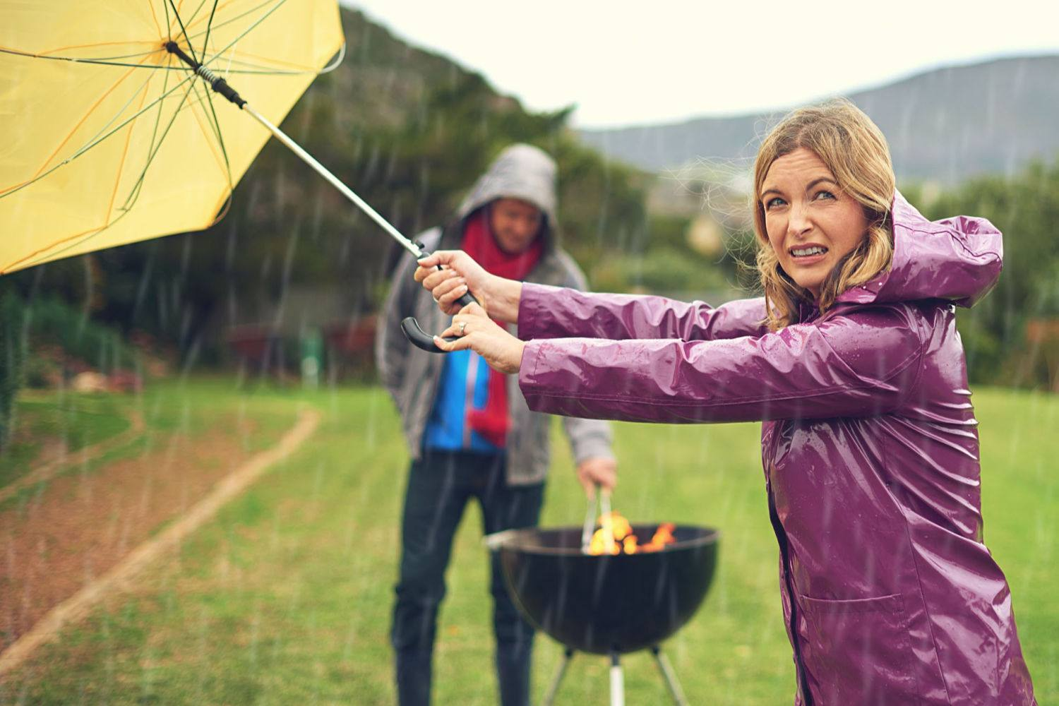 people grilling in the rain