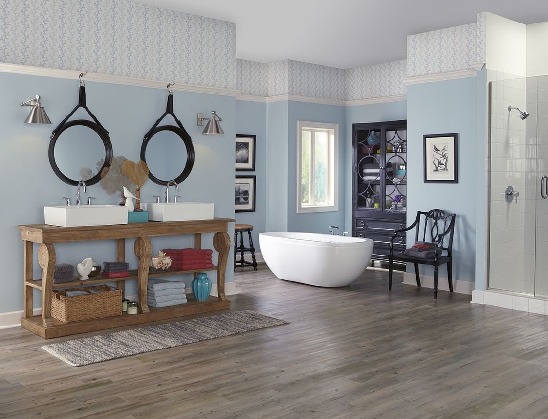 A bathroom with wallpaper accent near the ceiling, along with wooden floors, separate tub, and wooden vanities with farmhouse sinks.