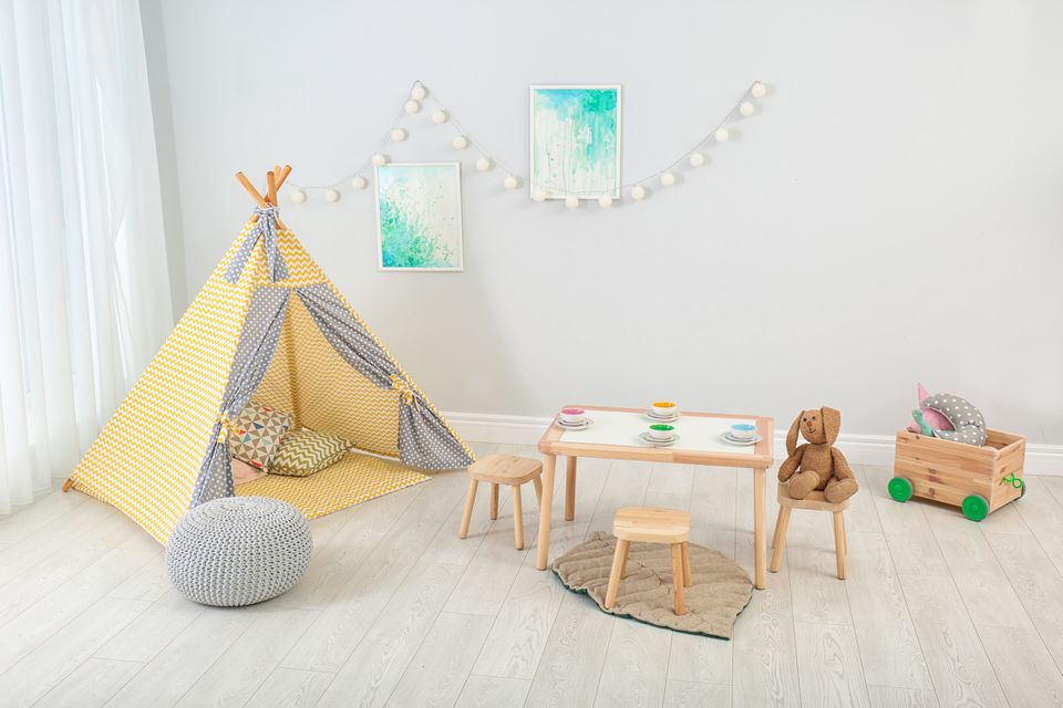 Cozy kids room interior with table, play tent and toys
