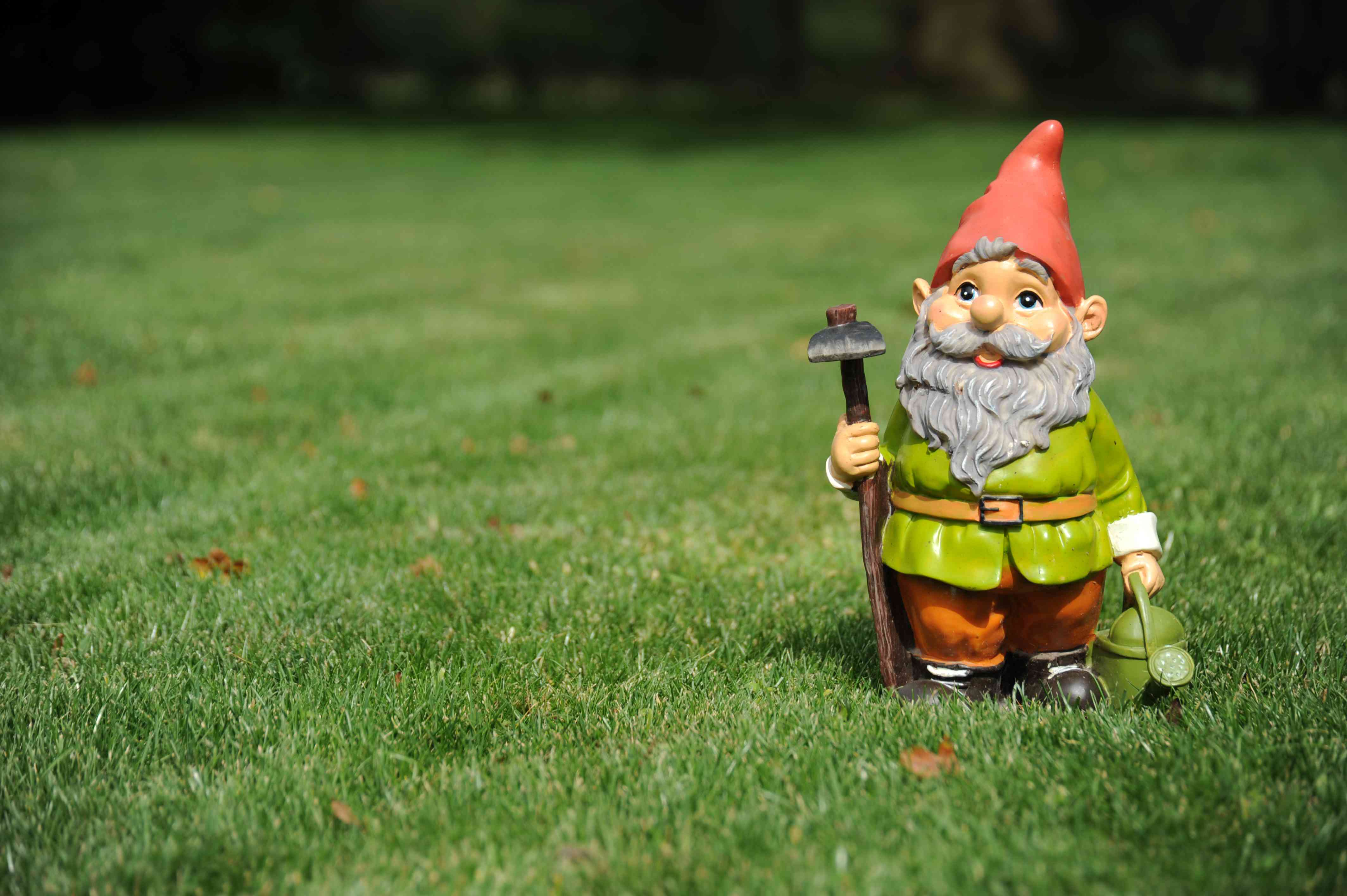 Close-up of garden gnome holding pickax and watering can