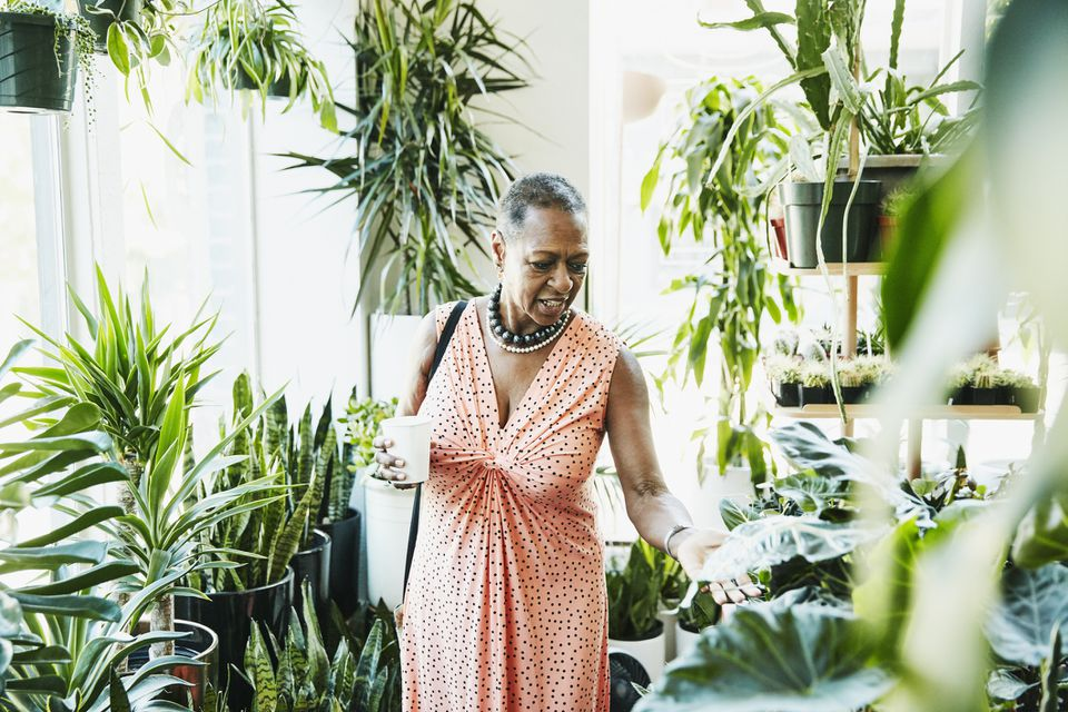 Senior woman touching plant leaf while shopping in plant store