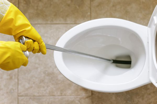 Toilet auger inserted into toilet held with yellow rubber gloves