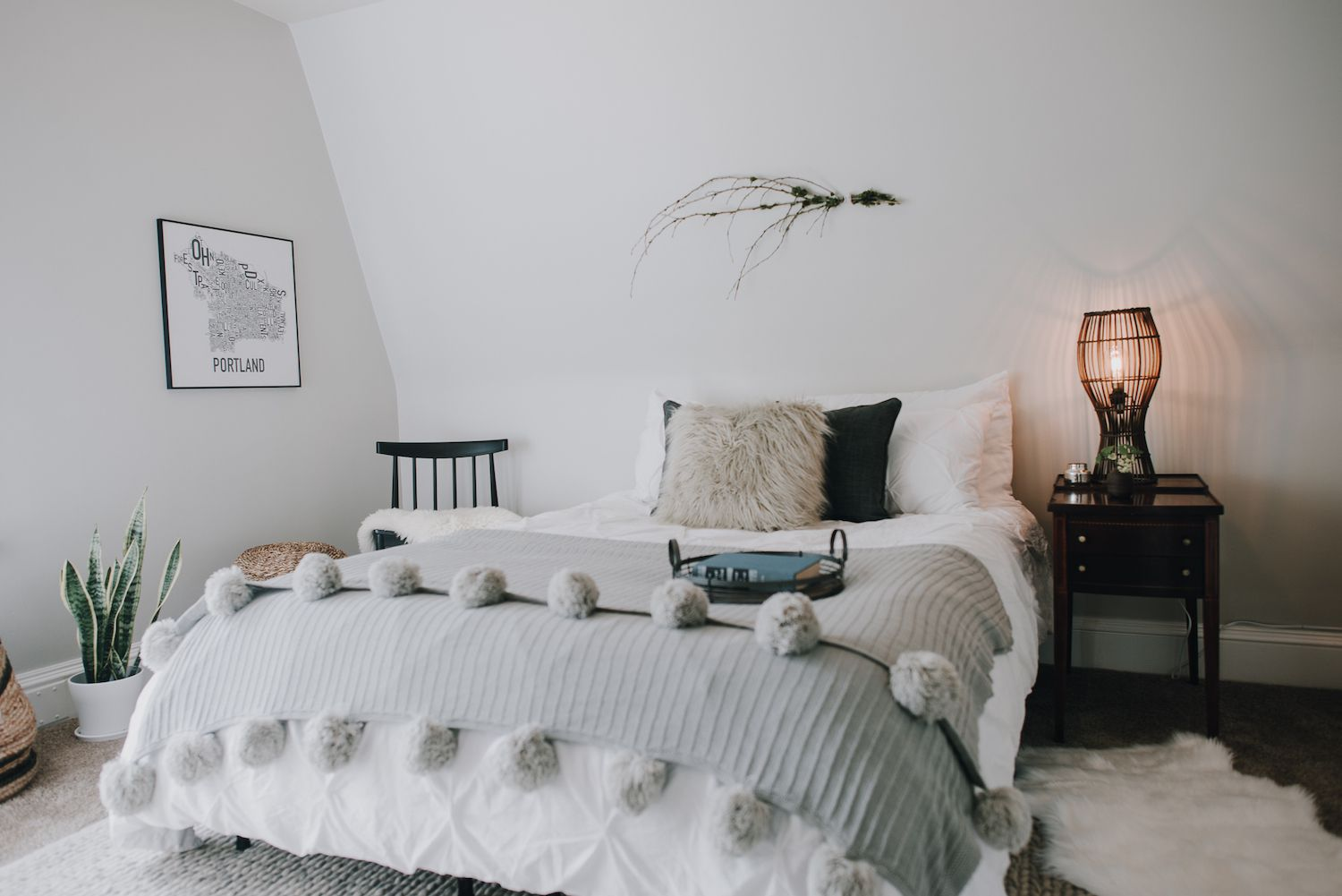 modern bedroom with soft textures: furry pillow, gray blanket with pom pons on the end. Cool tones