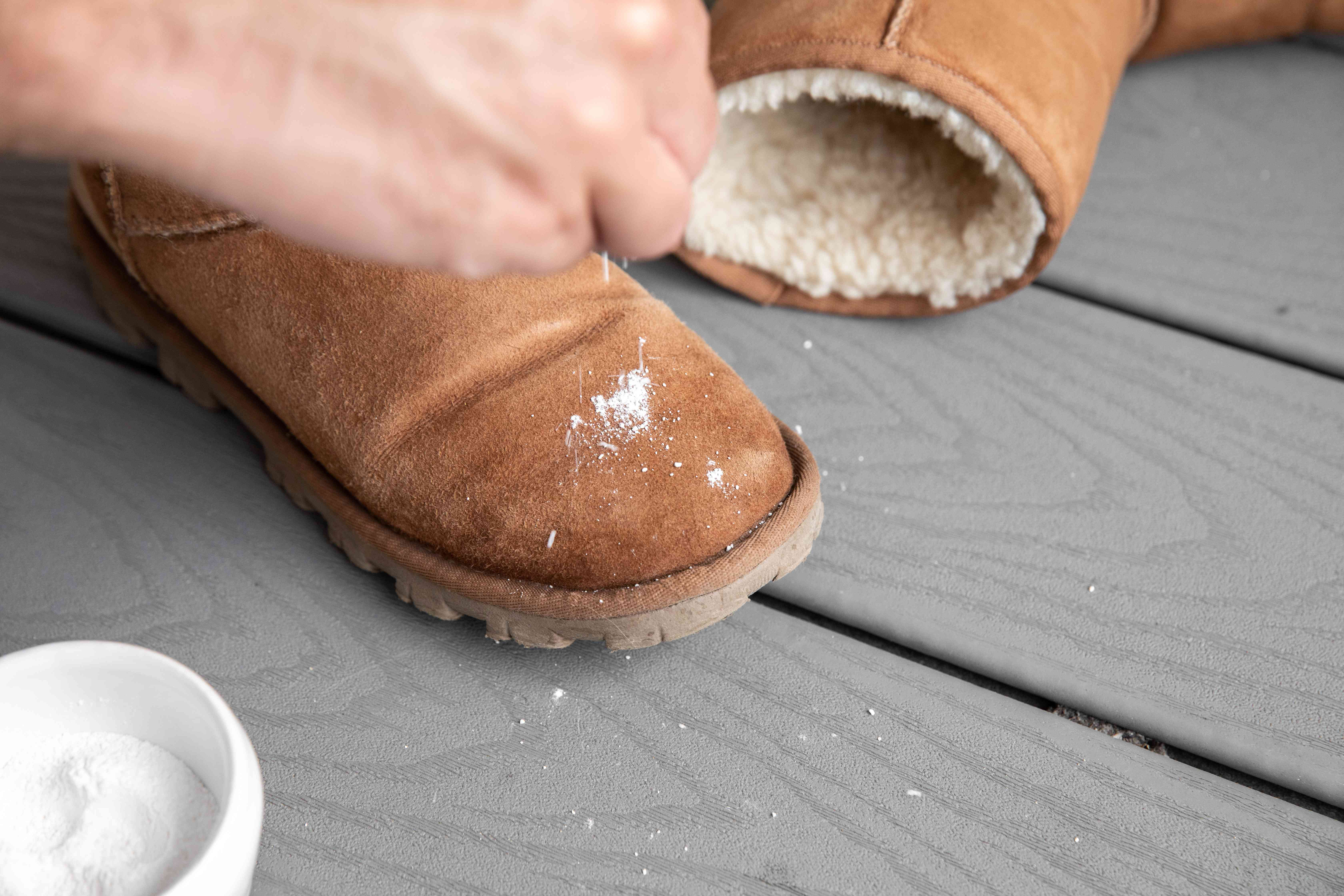 Someone sprinkling a boot with baby powder