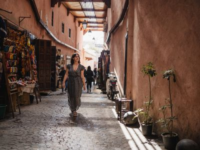 front view of young woman walking in the Marrakech souk with a long dress