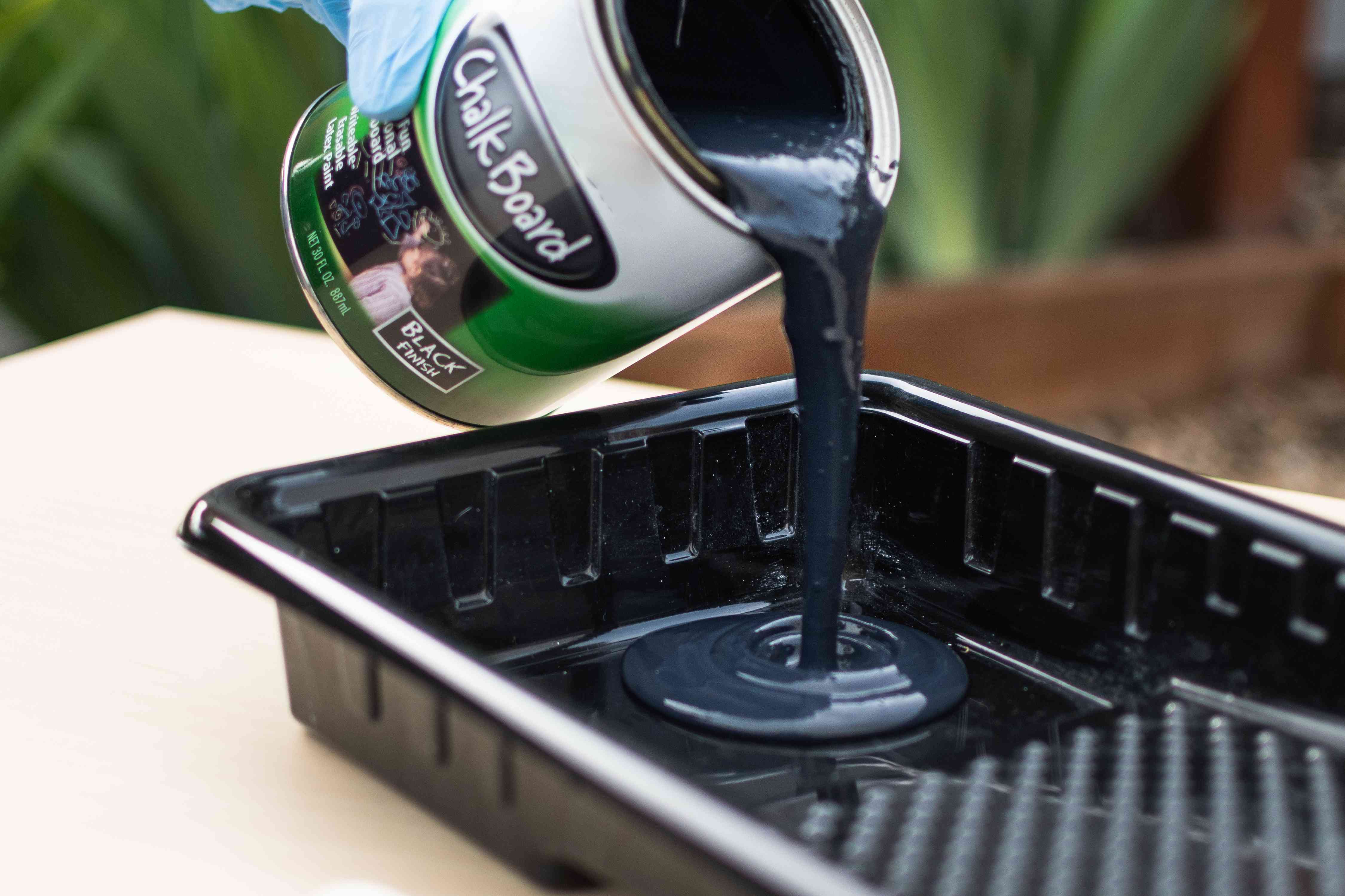 Black chalkboard paint poured into paint tray