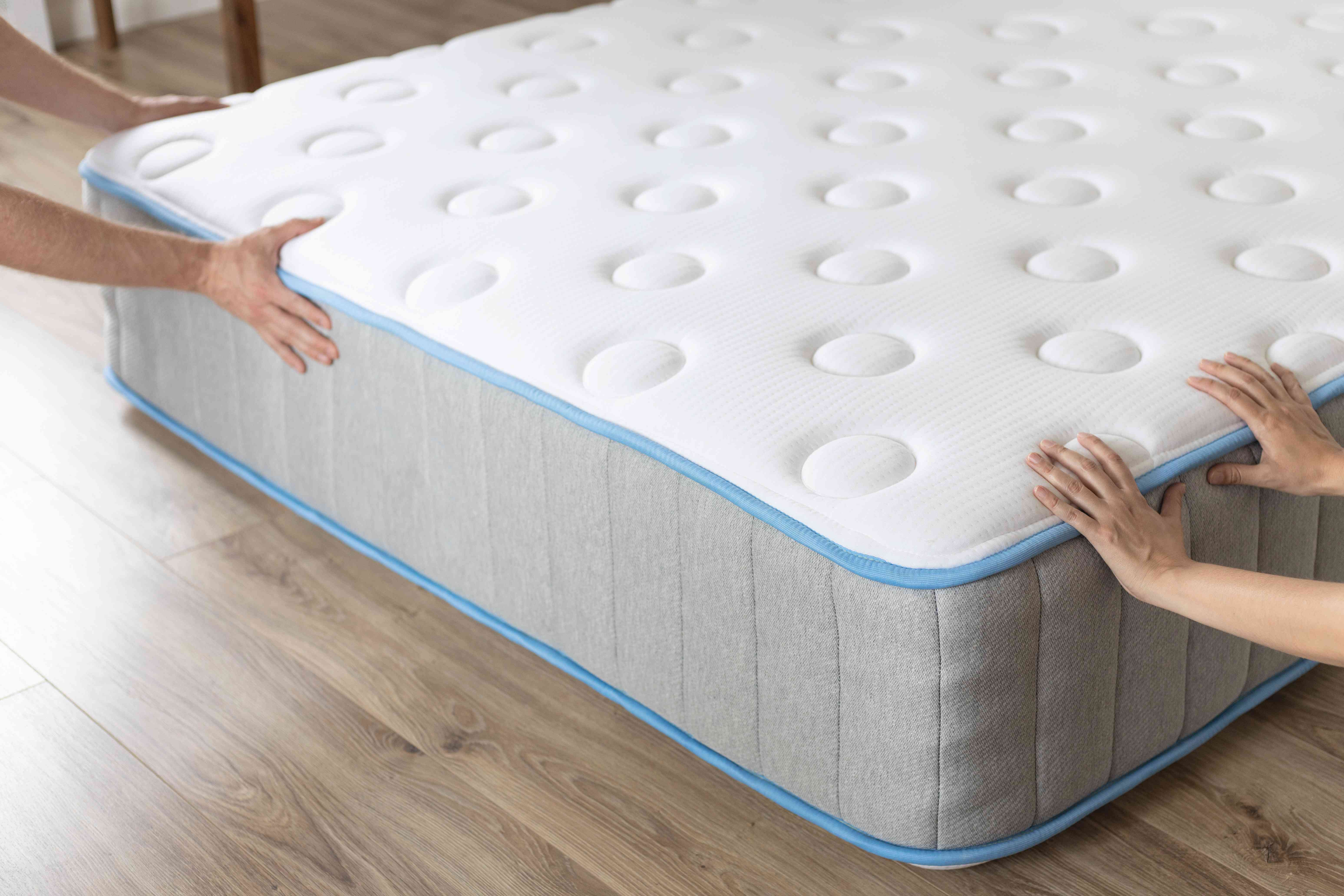 Two sets of hands moving mattress on wooden floor