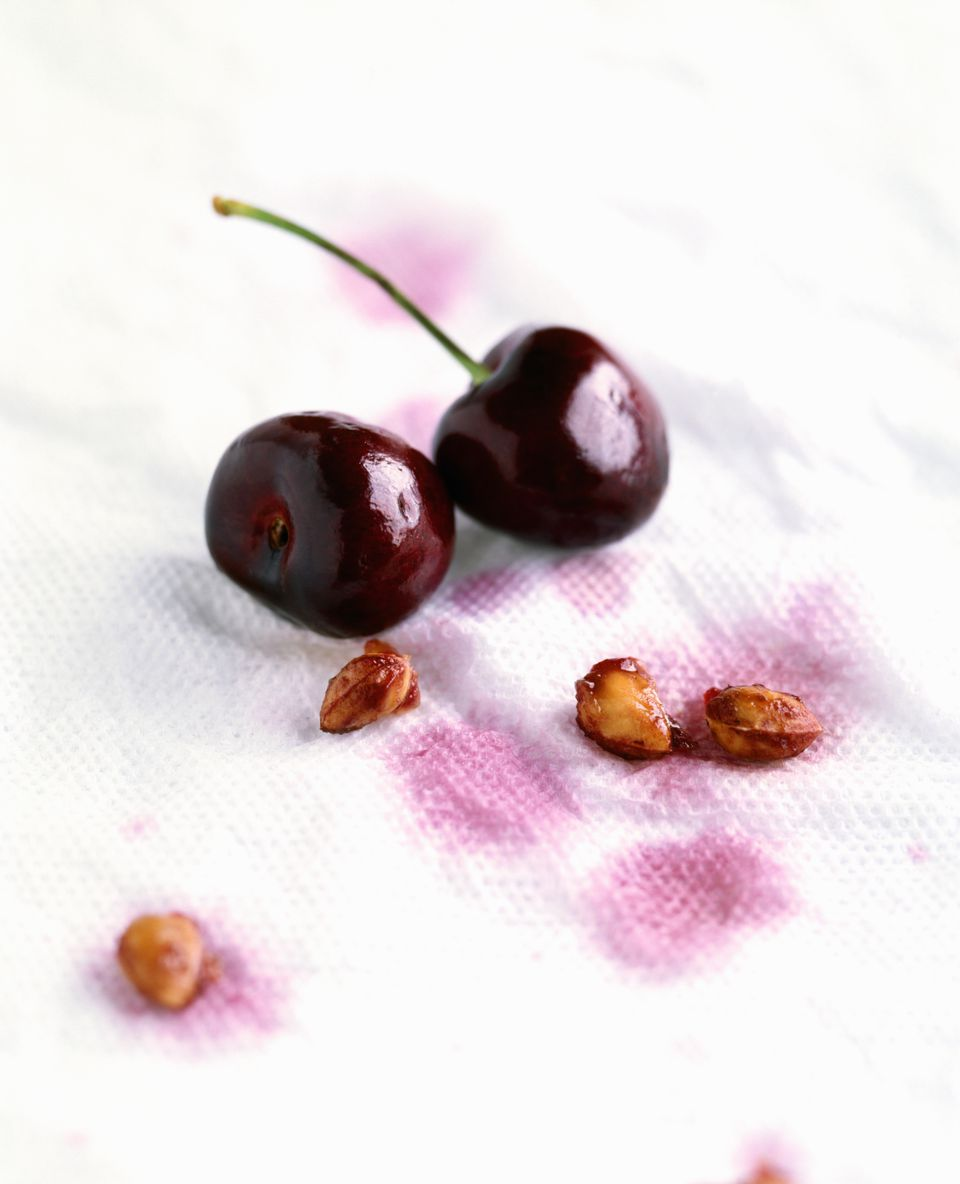 Cherries and pits on paper napkin, close up, studio shot