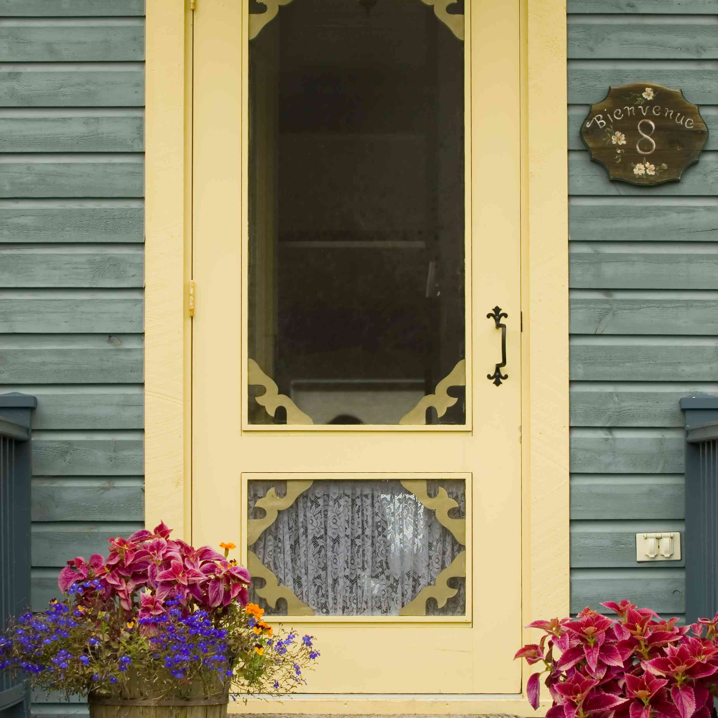 A farmhouse-style pale yellow door on a blue-gray house