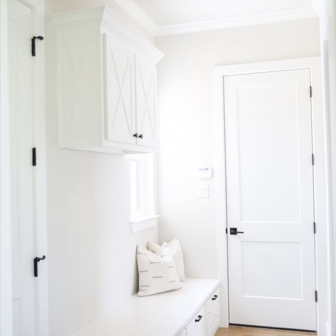 All white mudroom with bench and cabinetry.