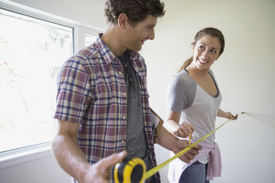 Couple measuring with tape measure