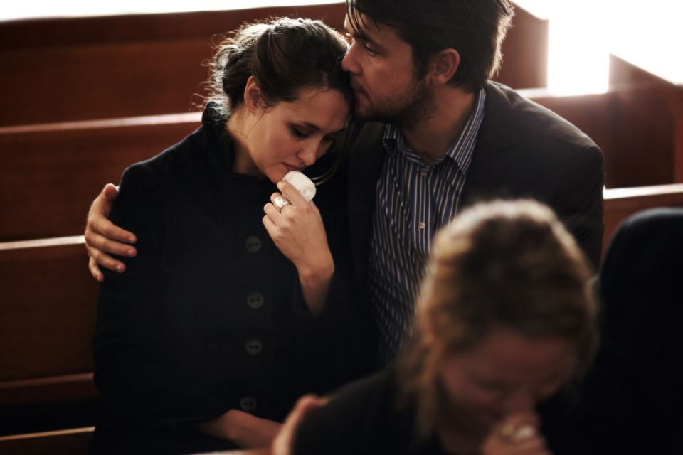 Man consoling a woman in a church pew at a funeral.