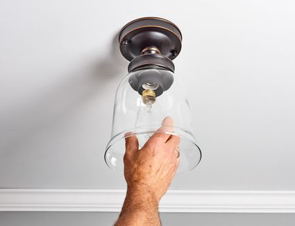 New light bulb being changed out of light socket in ceiling