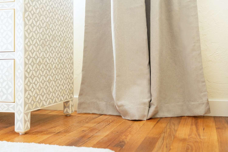 Tan drapes touching wooden floor near dresser
