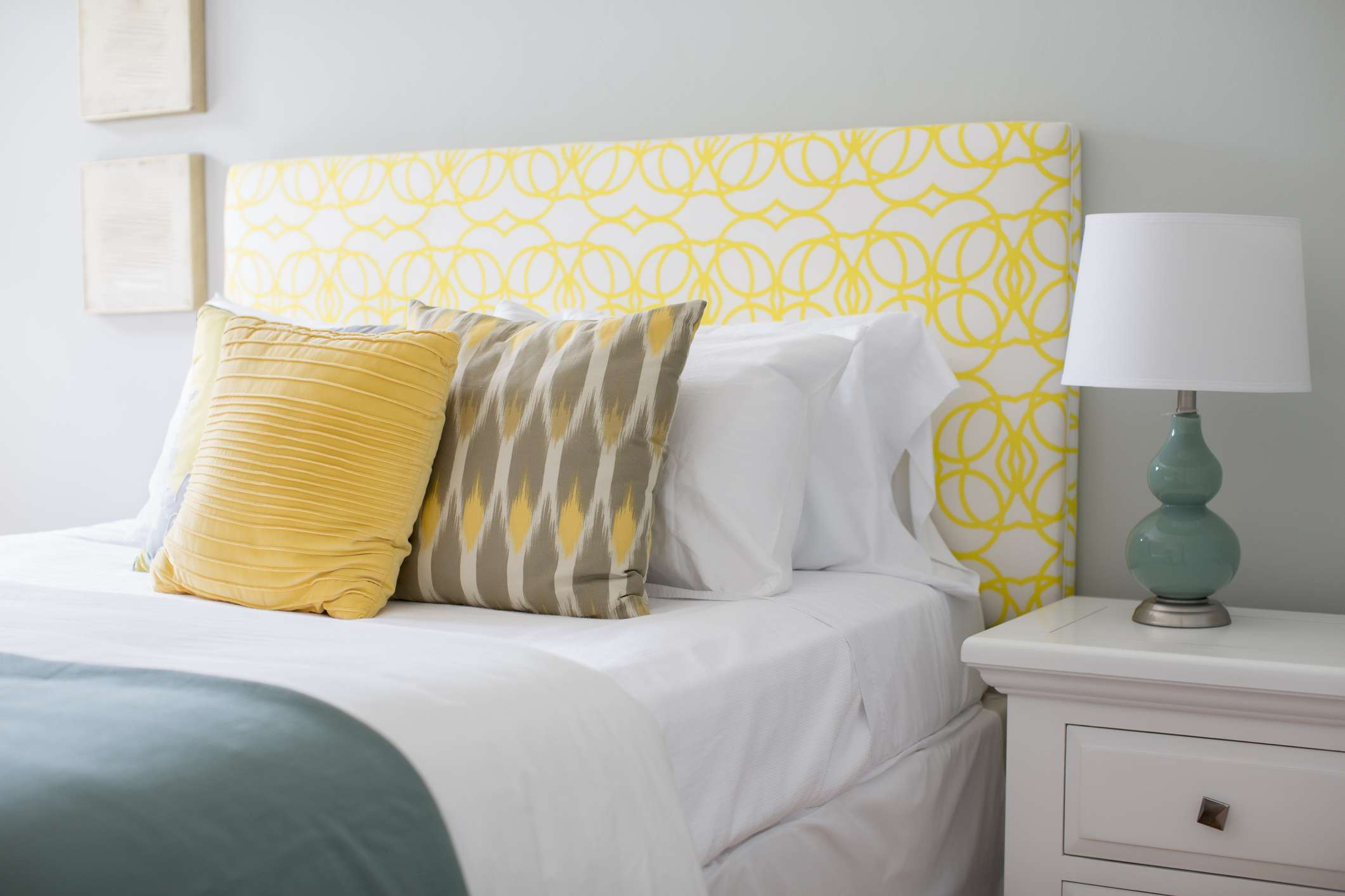bed with yellow headboard and turquoise accents