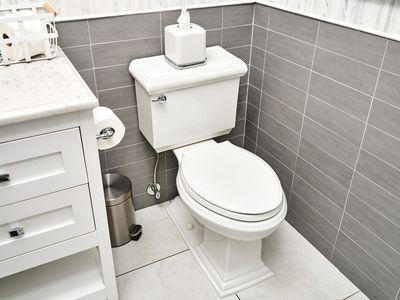 White toilet in gray wall tiled bathroom assessed for hairline crack