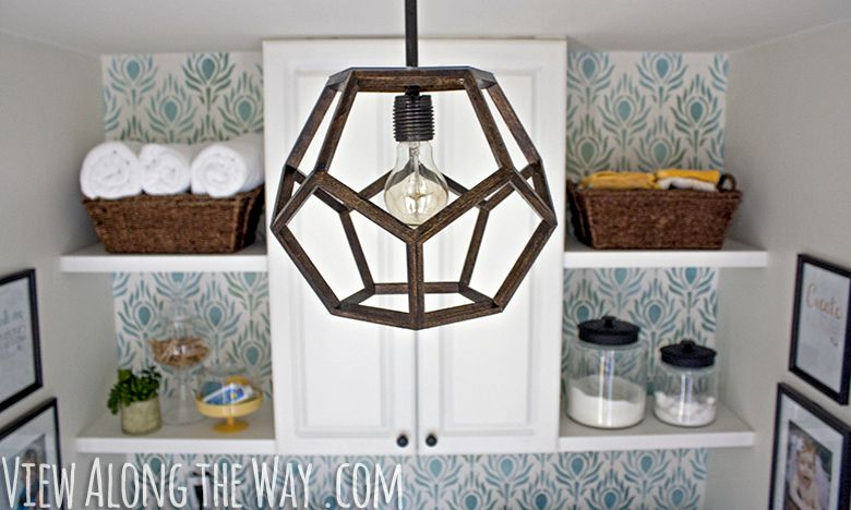 Light fixture hanging above laundry room along with baskets and detergent on shelving.