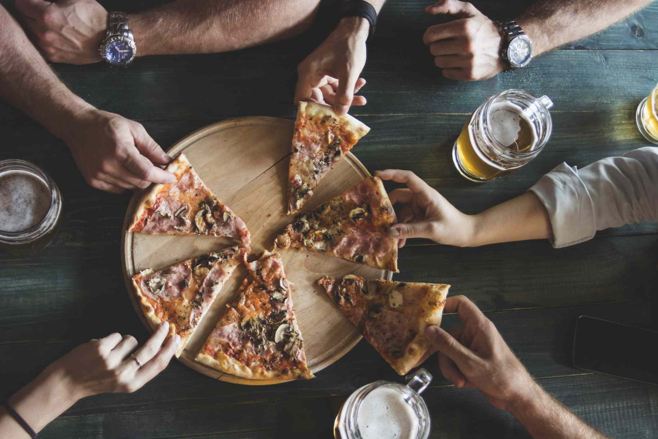 An overhead shot of friends drinking beer and eating pizza.