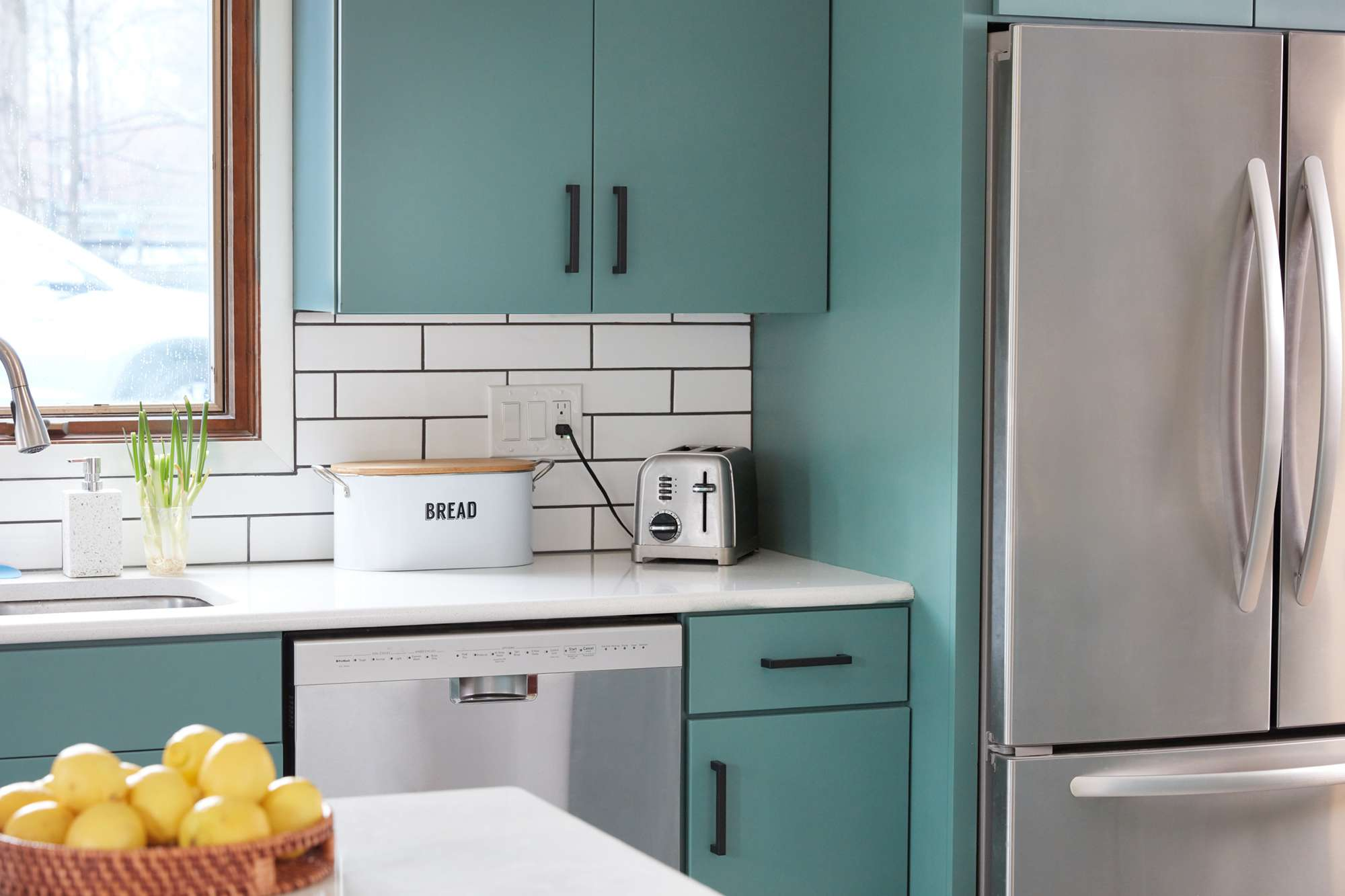 Stainless steel refrigerator and dishwasher appliances surrounded by mint green cabinets