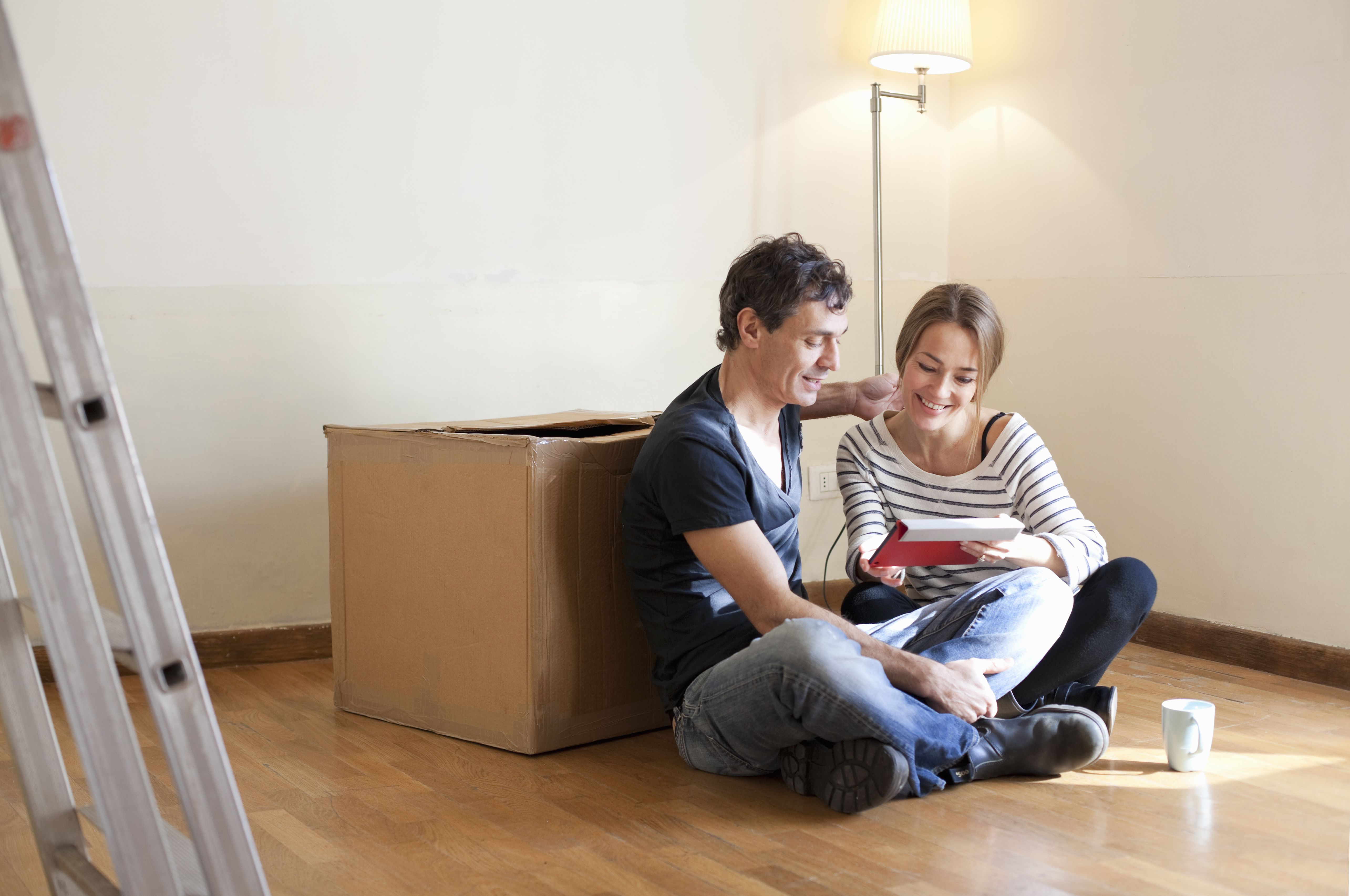 couple sitting on floor in their new, empty house