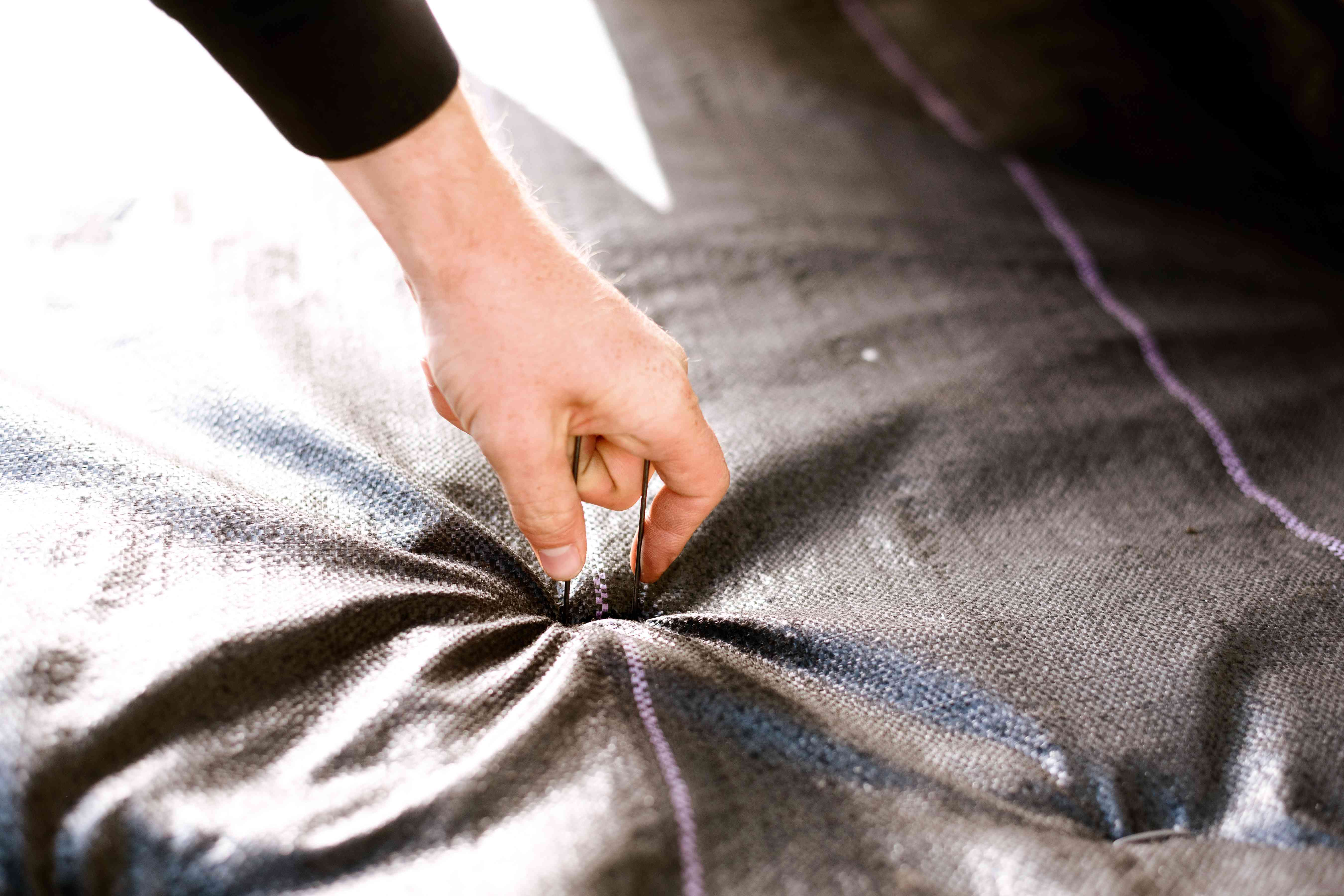 placing staples in the landscaping fabric