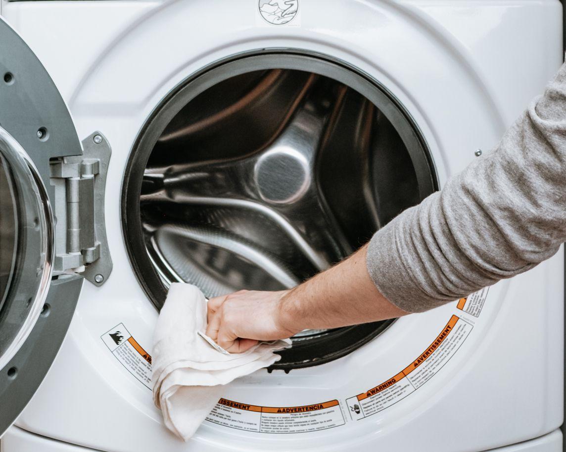 persona que limpia una lavadora con vinagre